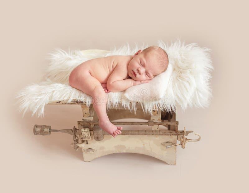 Neugeborenes Baby auf Gewichtsskala lizenzfreie stockfotografie