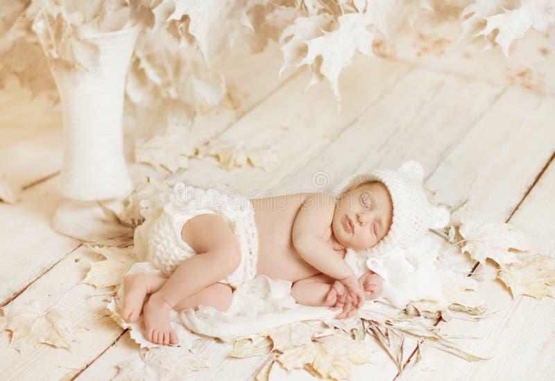 Neugeborenes Baby, das auf Blättern über weißem hölzernem schläft lizenzfreies stockbild