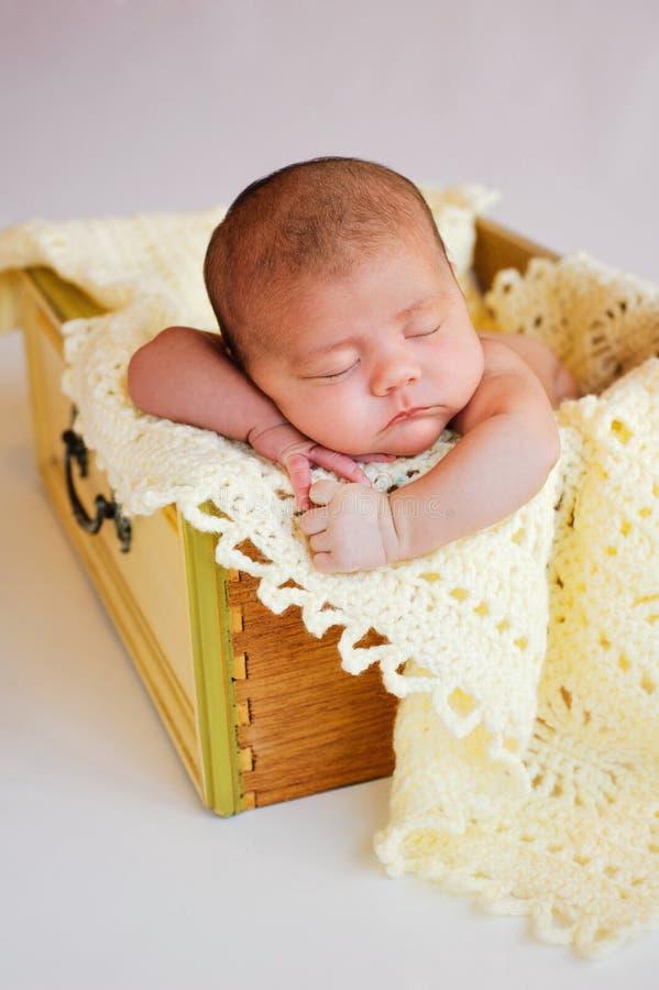 Neugeborenes Baby, das im gelben Fach schläft stockbild