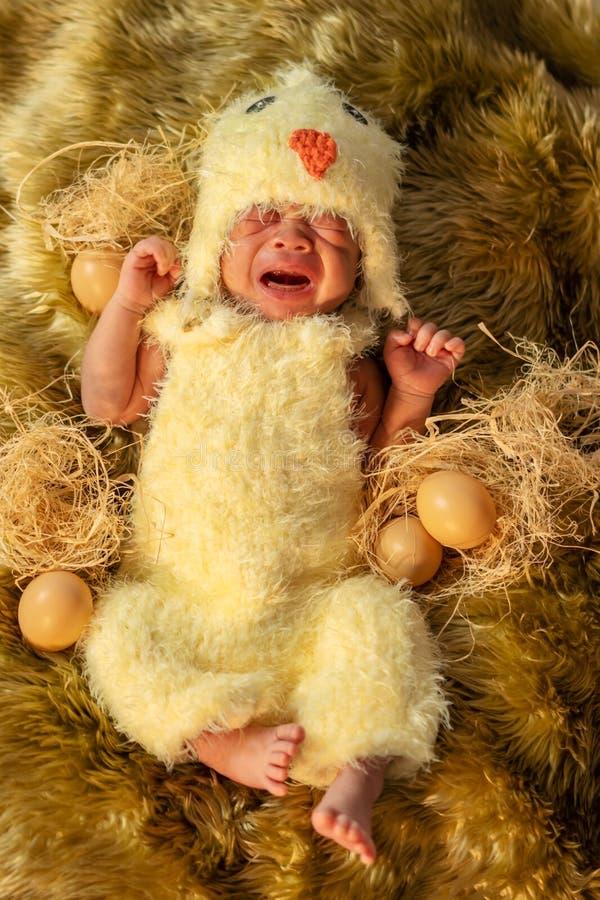 Neugeborenes Baby, das im Hühnerkostüm schläft auf Pelzbett schreit stockbild