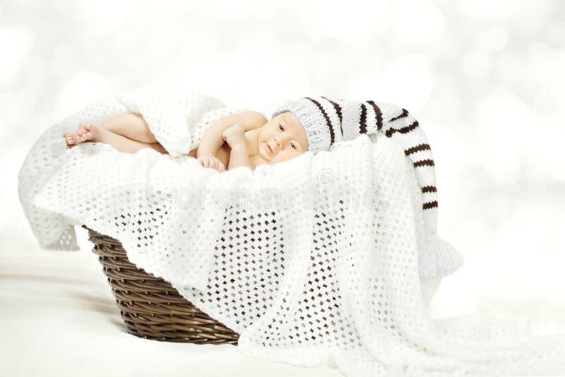 Neugeborenes Baby, das im Korb, neugeborenes Kinderwoolen Strickmütze liegt stockfoto