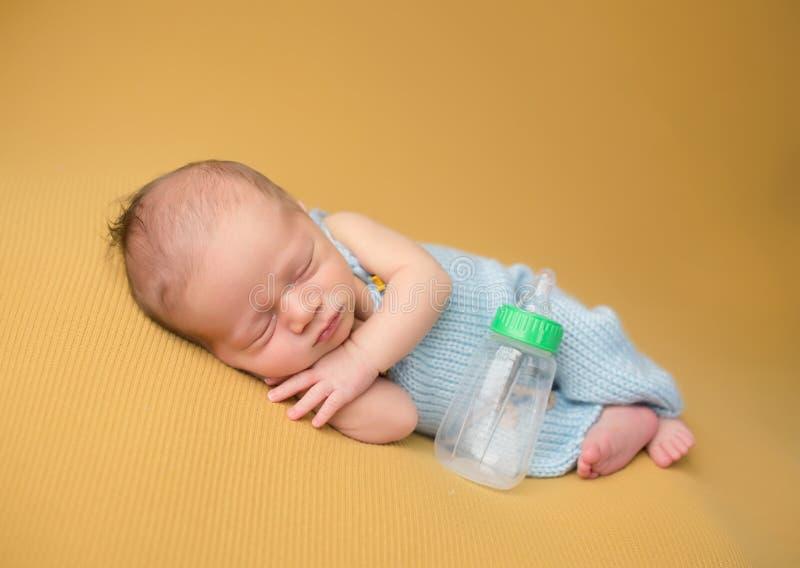 Neugeborenes Baby, das mit Flasche schläft stockbilder