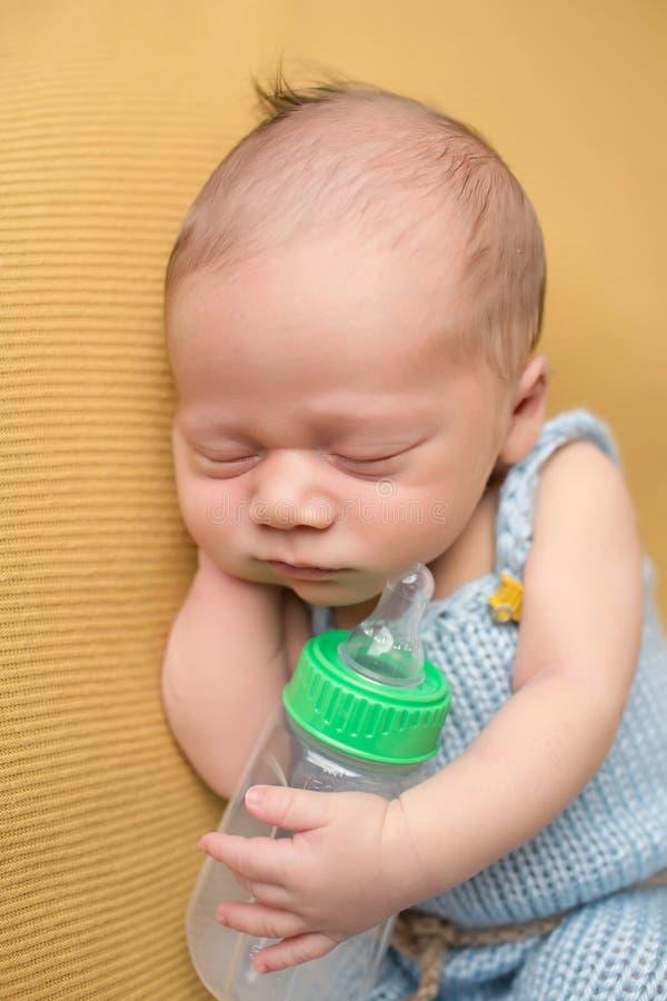 Neugeborenes Baby, das mit Flasche schläft stockfoto