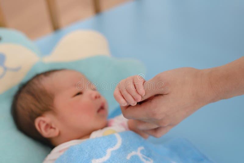 Neugeborenes Baby, das Mutter-Hand hält lizenzfreie stockfotos