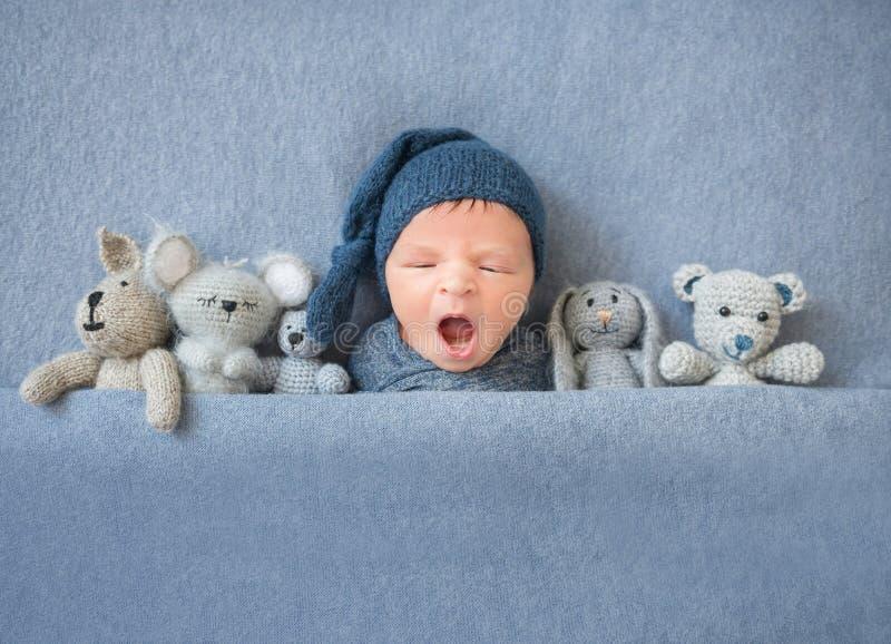 Neugeborenes Baby, das zwischen Plüschspielwaren gähnt und liegt lizenzfreies stockbild