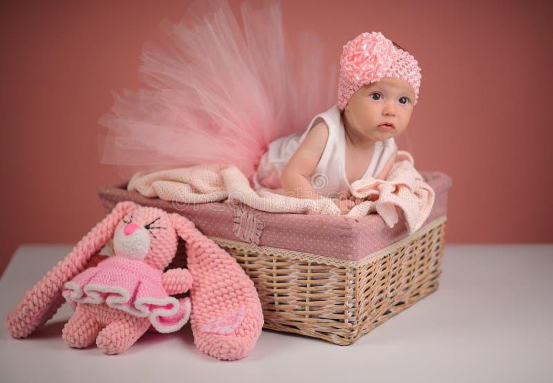 Neugeborenes Baby in einem Korb auf rosa Hintergrund lizenzfreies stockfoto