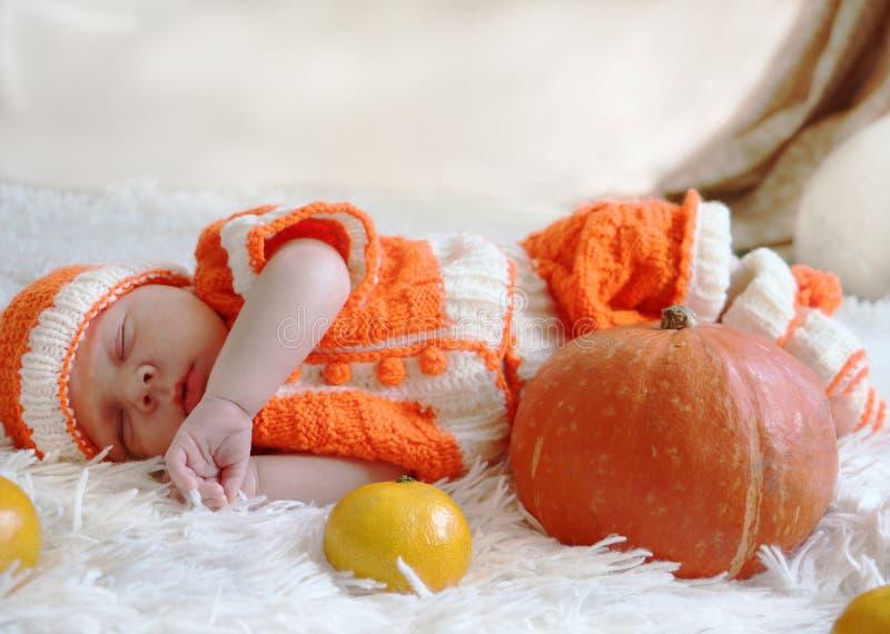 Neugeborenes Baby in gestricktem orange Kostüm schlafend auf weißer Decke lizenzfreie stockfotos