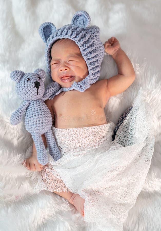 Neugeborenes Baby im Bärnhut schreiend auf Pelzbett stockfotografie