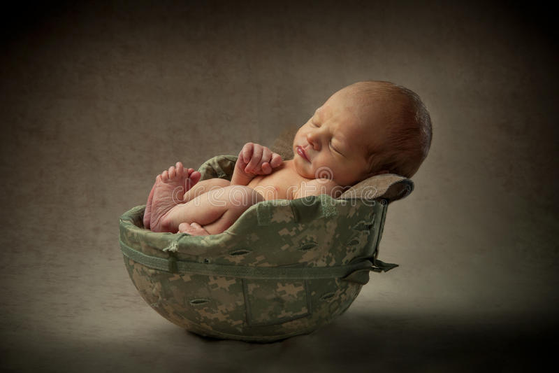 Neugeborenes Baby im Militärsturzhelm lizenzfreie stockfotos