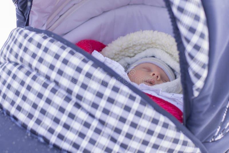 Neugeborenes Baby schläft auf einem Weg in einem Pram an einem Wintertag lizenzfreies stockfoto