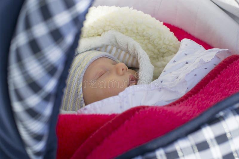 Neugeborenes Baby schläft auf einem Weg in einem Pram an einem Wintertag stockfotos