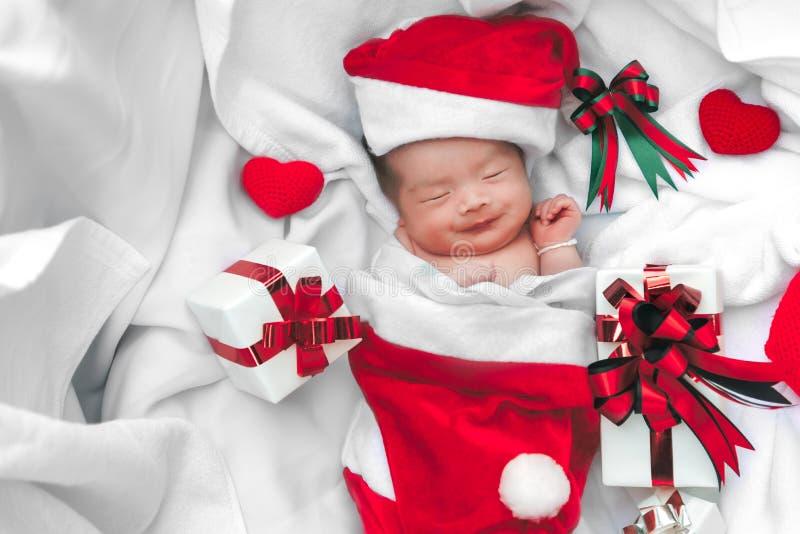 Neugeborenes Babygesicht Schlafens im Weihnachtshut mit Geschenkbox von Santa Claus- und Garnherzen auf wei?em weichem Tuch Nette stockfoto