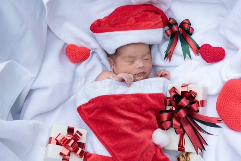 Neugeborenes Babygesicht Schlafens im Weihnachtshut mit Geschenkbox von Santa Claus- und Garnherzen auf wei?em weichem Tuch Nette stockfotografie