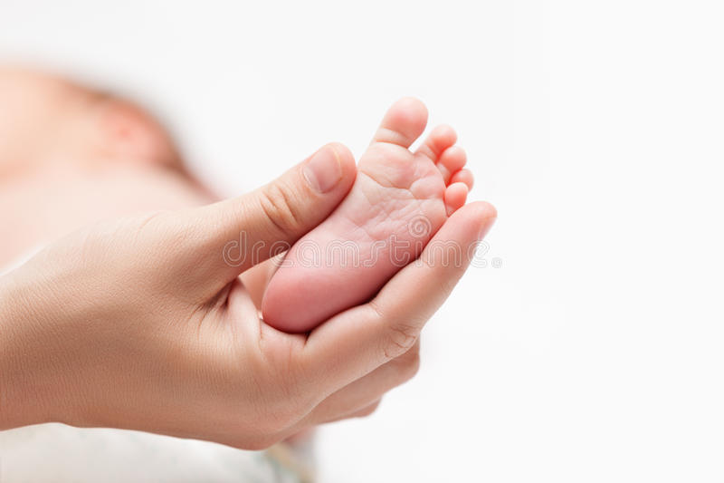 Neugeborenes Babykind wenig Fuß mit Ferse und den Zehen in der Mutterhand lizenzfreies stockfoto
