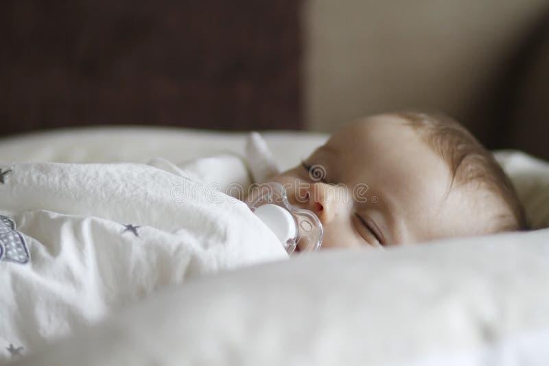 Neugeborenes Kind, das mit Friedensstifter schläft lizenzfreie stockbilder