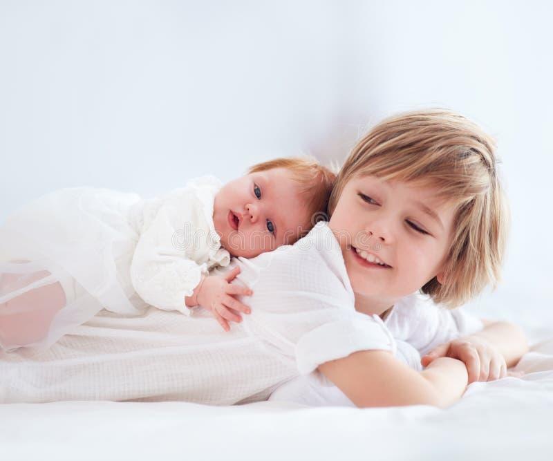 Neugeborenes kleines Schwesterchen, das auf nettem älterem Bruder liegt stockbild