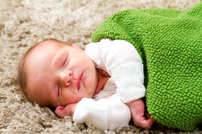 Neugeborenes Schätzchen in der grünen Decke stockbilder