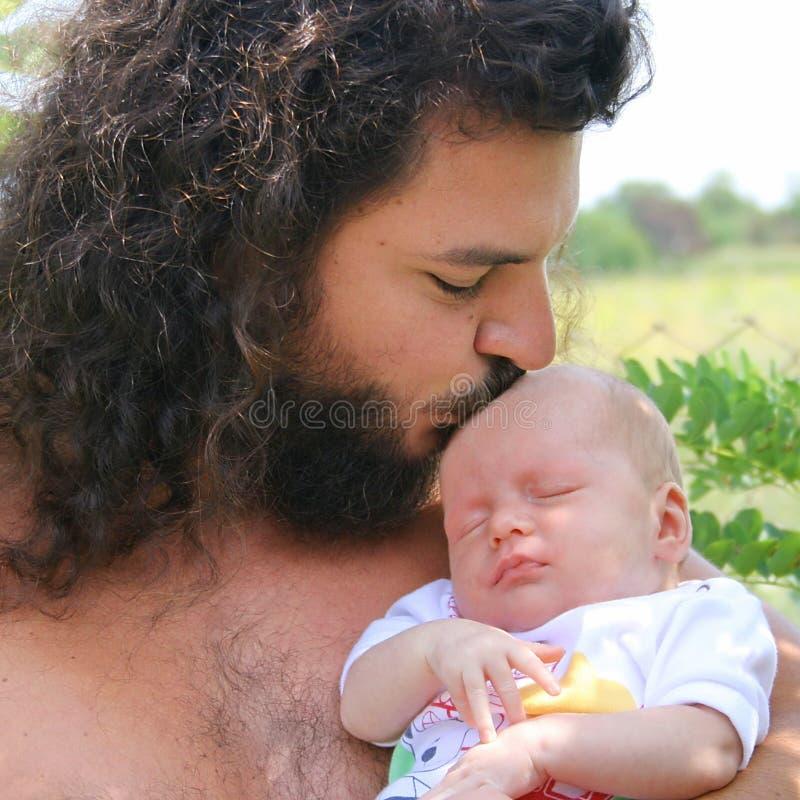 Neugeborenes Schätzchen schläft in seiner Vaterhand stockbild