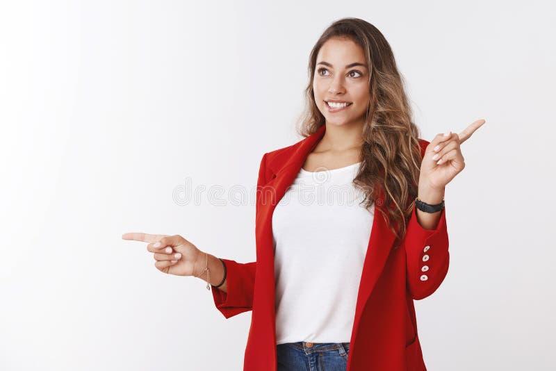 Neugierige attraktive gl?ckliche junge l?chelnde Frau, welche die schneidende Lippe der roten Jacke beiseite schaut das w?nschens stockfotografie