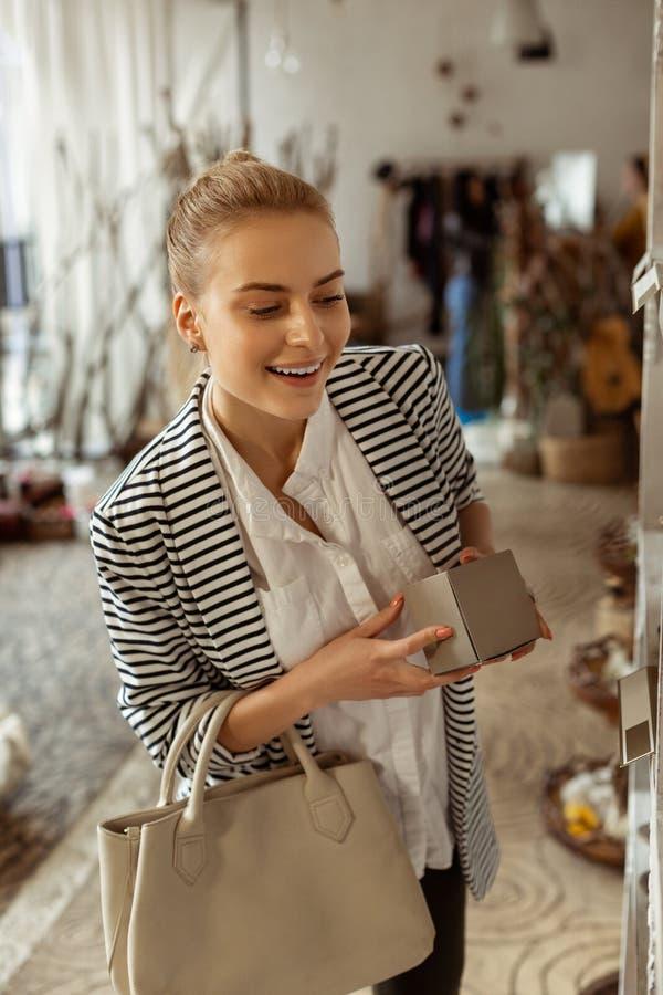 Neugierige Dame im weißen Hemd, das auf interessanten Produkten flüchtig blickt lizenzfreie stockfotografie