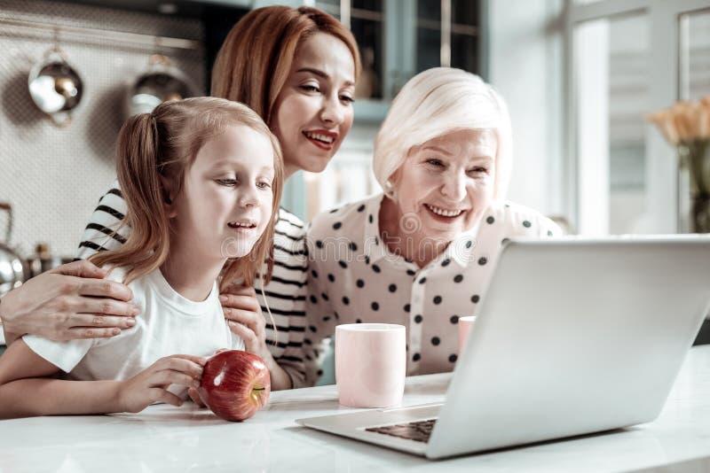 Neugierige dreiköpfige Familie, die zum Laptop beim Haben des Videoanrufs sich lehnt lizenzfreies stockfoto