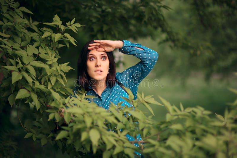 Neugierige eifersüchtige Frau, die von den Büschen ausspioniert stockbild