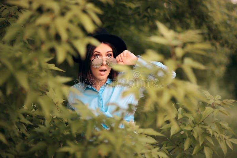 Neugierige eifersüchtige Frau, die von den Büschen ausspioniert stockfotos