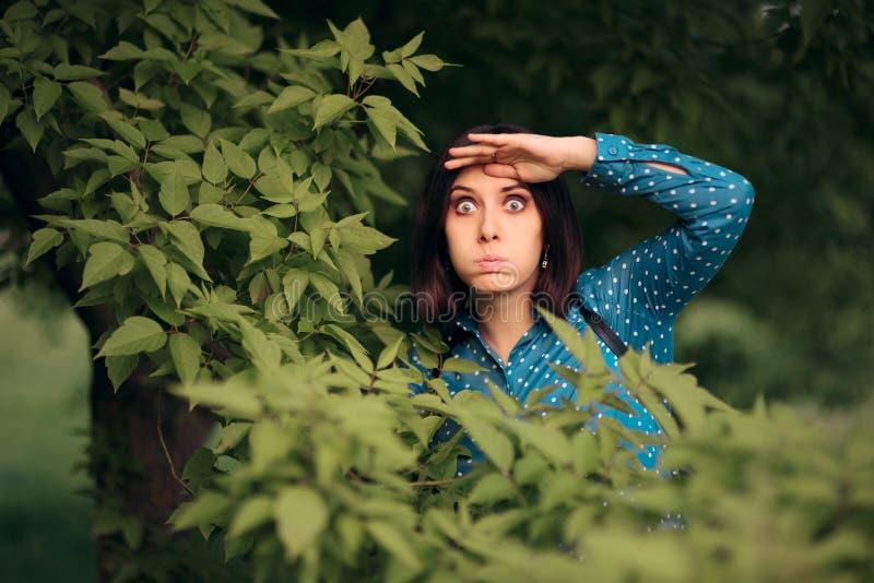 Neugierige eifersüchtige Frau, die von den Büschen ausspioniert stockbilder