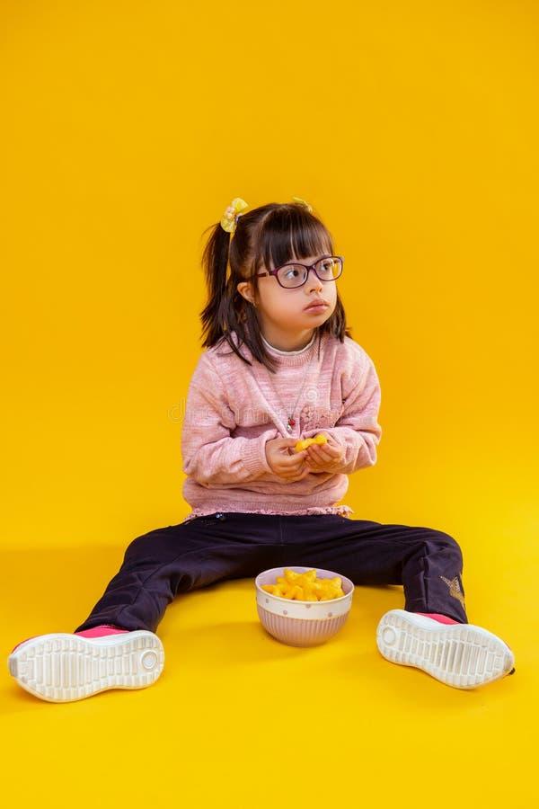 Neugierige ernste kleine Dame, die auf bloßem Boden gegen Schüssel sitzt stockfotografie