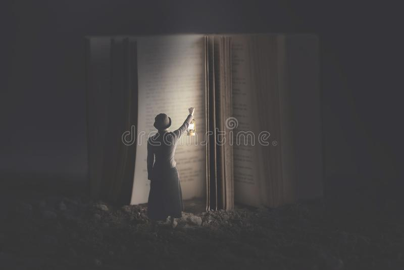 Neugierige Frau belichtet mit einer Laterne ein riesiges Buch nachts lizenzfreie stockbilder