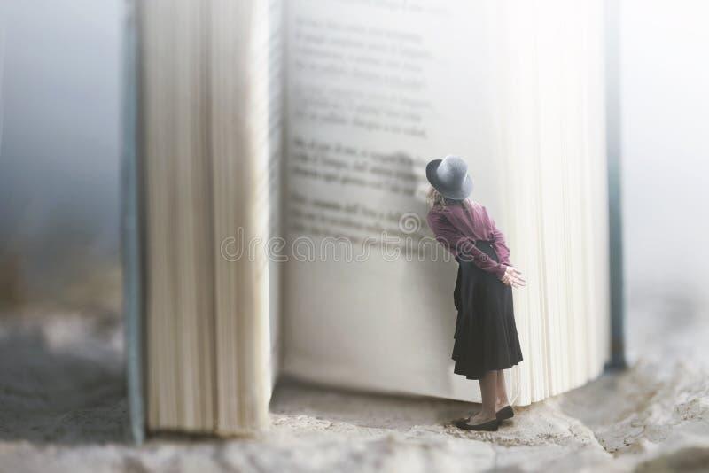 Neugierige Frau liest ein riesiges Buch lizenzfreies stockfoto