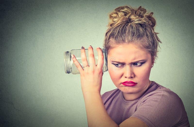 Neugierige Frau mit Glasgefäß hört auf Klatsch hinter der Wand lizenzfreie stockfotografie