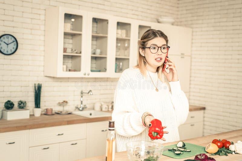 Neugierige gesprächige Frau, die Gespräch durch Smartphone hat lizenzfreies stockbild