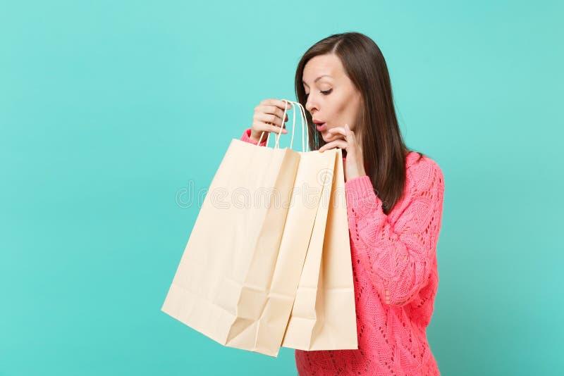 Neugierige junge Frau in der gestrickten rosa Strickjacke, die in der Hand auf Einkaufstasche mit der Aufschrift des schriftliche lizenzfreies stockfoto