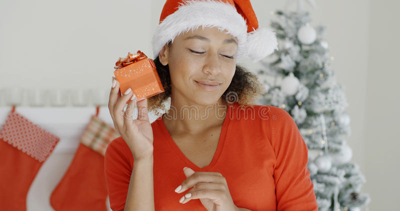 Neugierige junge Frau, die ihr Weihnachtsgeschenk rüttelt lizenzfreie stockbilder