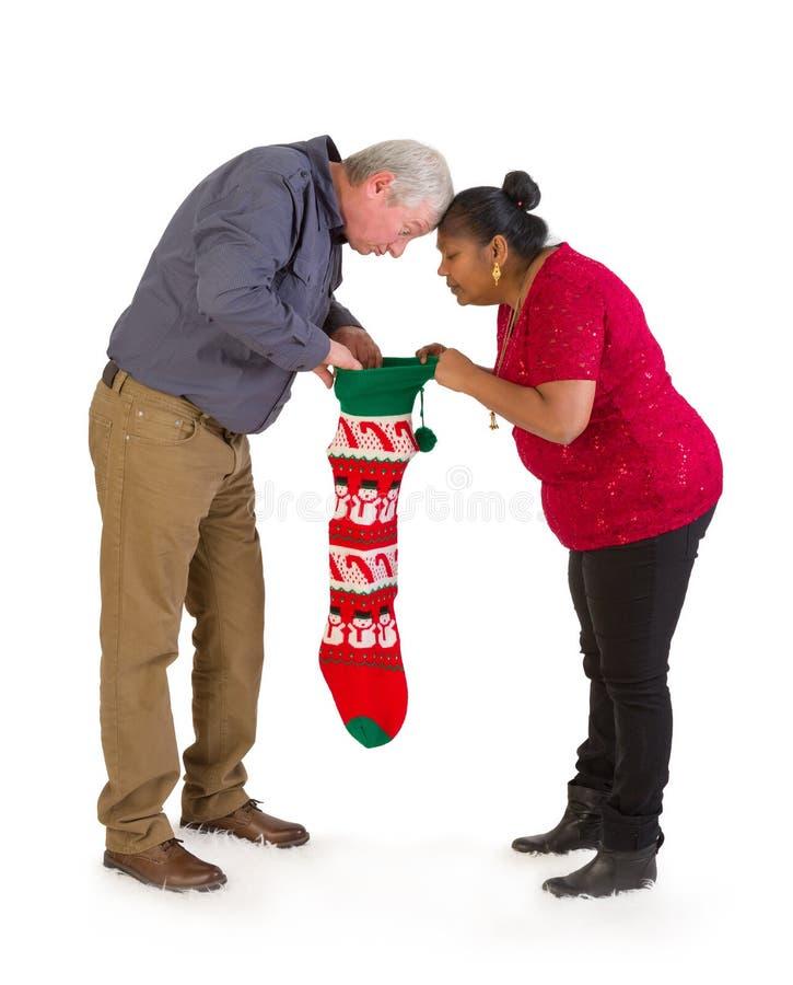 Neugierige Paare, die im Weihnachtsstrumpf schauen lizenzfreies stockbild