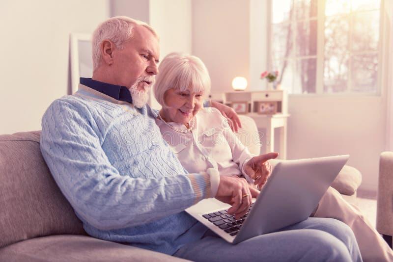 Neugierige Paare Pensionäre, die mit Laptop arbeiten stockbild