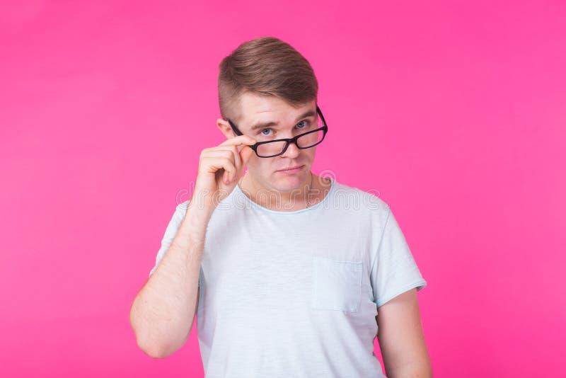 Neugieriger hübscher junger Mann im blauen Hemd, das über gesenkten Brillen mit einer skeptischen, misstrauischen Haltung schaut stockfoto