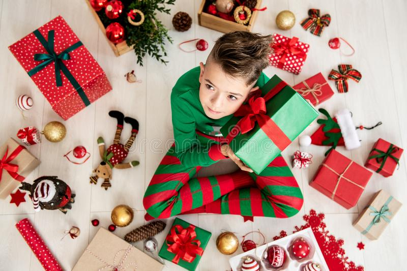 Neugieriger Junge, der Weihnachtspyjamas sitzen auf dem Boden am Weihnachtstag, sein Weihnachtsgeschenk rüttelnd, um zu hören trä stockbilder