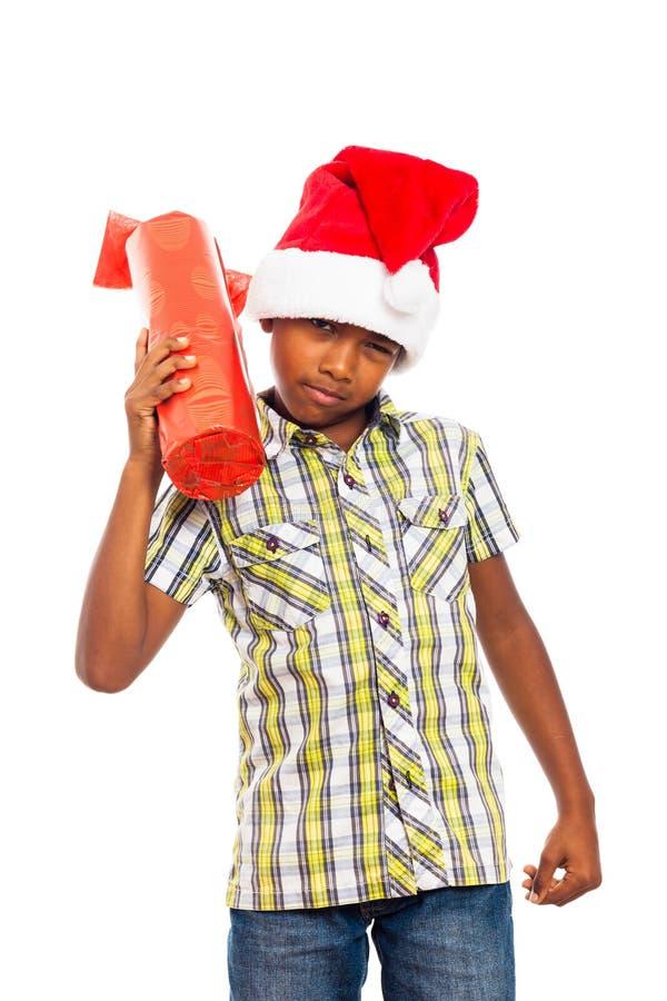 Neugieriger Junge mit Weihnachtsgeschenk lizenzfreies stockfoto