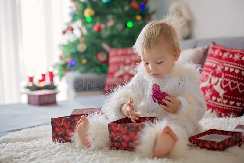 Neugieriger kleiner Kleinkindjunge, gekleidet im handgestrickten weißen Gesamten, liegend auf der Couch, die mit Geschenken spiel stockfotografie