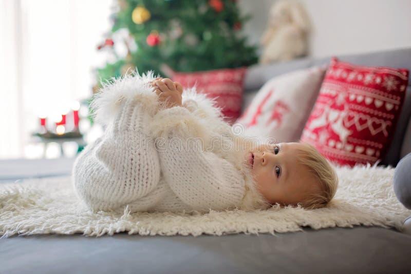 Neugieriger kleiner Kleinkindjunge, gekleidet im handgestrickten weißen Gesamten, liegend auf der Couch, die mit Geschenken spiel stockbild