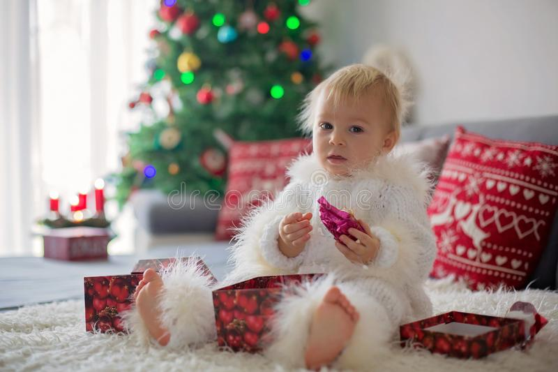 Neugieriger kleiner Kleinkindjunge, gekleidet im handgestrickten weißen Gesamten, liegend auf der Couch, die mit Geschenken spiel lizenzfreies stockbild