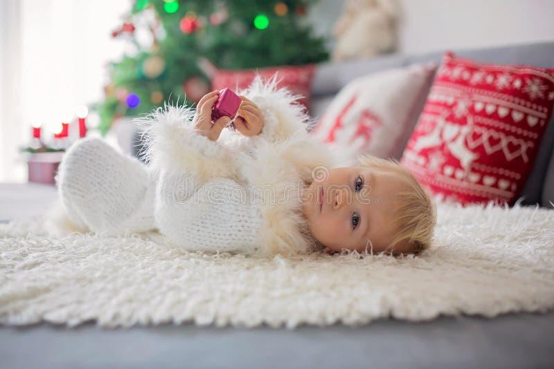 Neugieriger kleiner Kleinkindjunge, gekleidet im handgestrickten weißen Gesamten, liegend auf der Couch, die mit Geschenken spiel lizenzfreie stockfotos