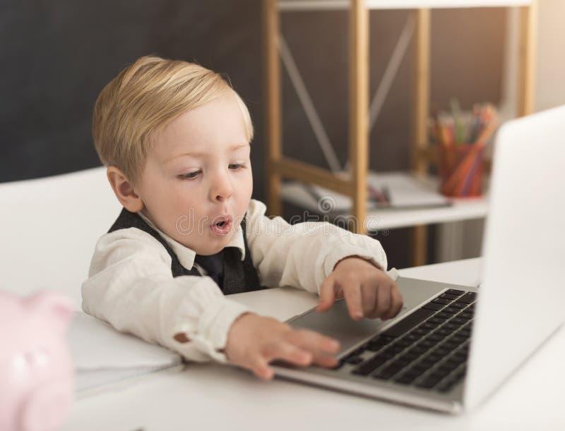 Neugieriger Kleinunternehmer in formalem bei Tisch mit Laptop stockbilder