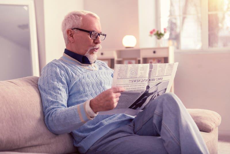 Neugieriger Senior überrascht mit Materialien in der Zeitung lizenzfreie stockbilder