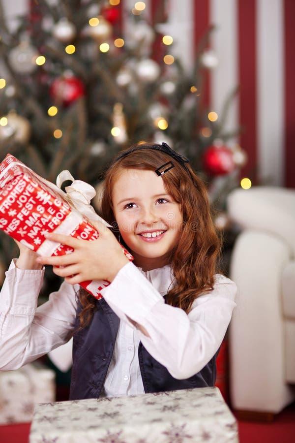 Neugieriges kleines Mädchen, das ihr Weihnachtsgeschenk rüttelt stockfotos