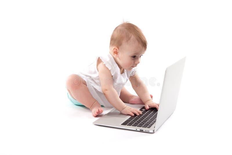 Neugieriges lächelndes Kind, das nahe dem Laptop auf einem weißen backgro sitzt stockfoto