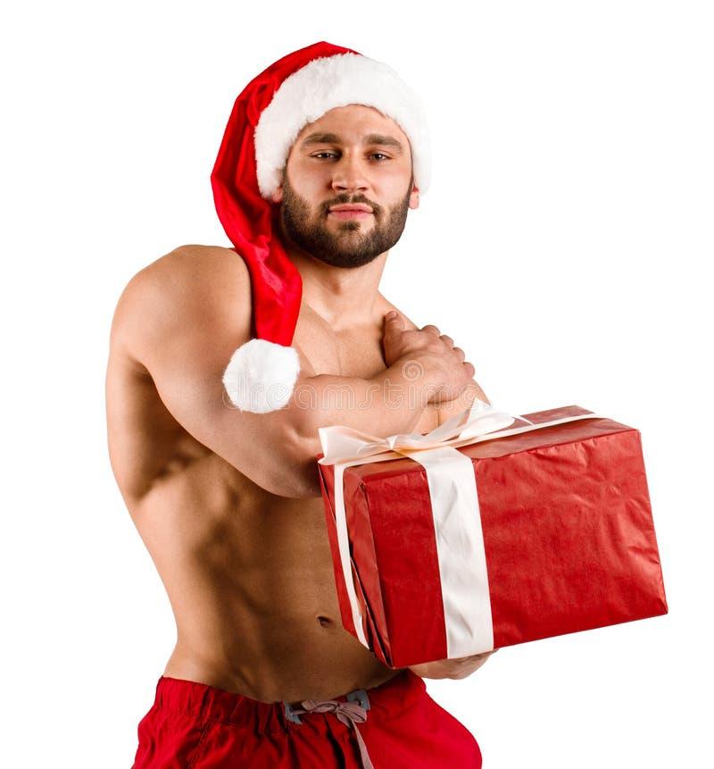 Neujahrsgeschenk vom weißen Kerl der Eignung, der Santa Claus-Hut, lokalisiert trägt lizenzfreie stockfotos