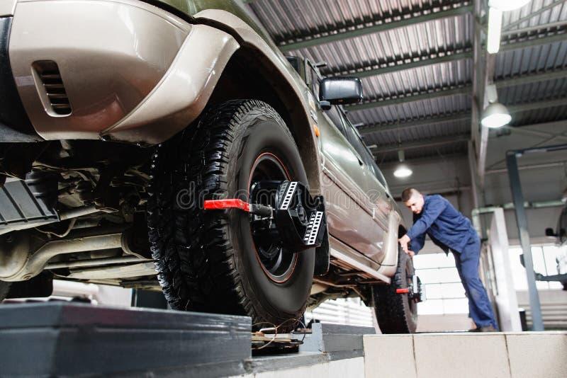 Neumático afianzado con abrazadera con el alineador para la alineación de rueda auto fotos de archivo libres de regalías